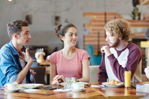 Group of millennials talking by lunch in new cafe or diner